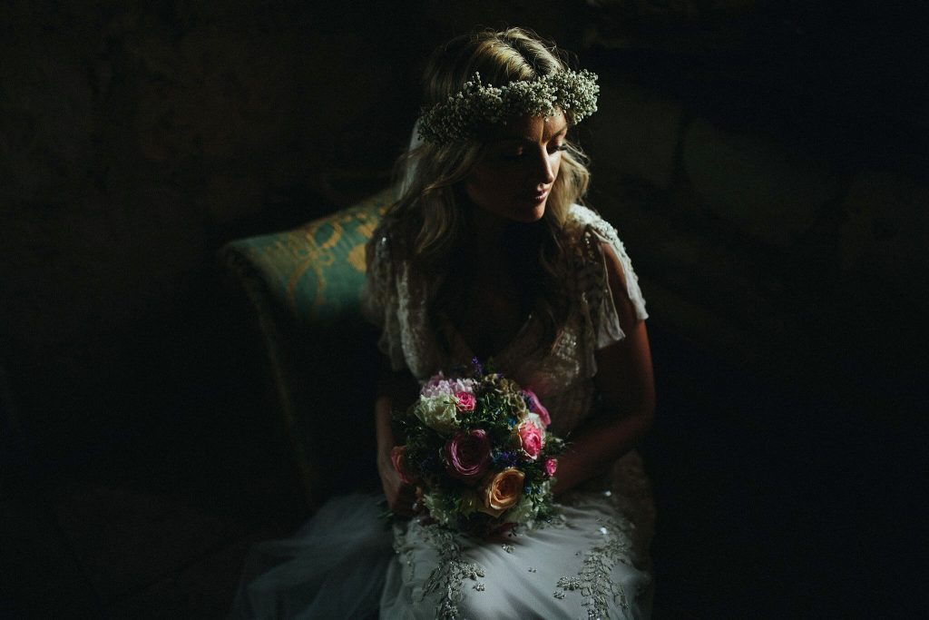 Dark portrait of bride with flowers in hair by Petar Jurica