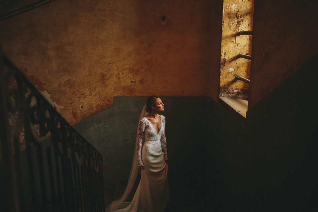 warm lit portrait of bride looking at window by Petar Jurica